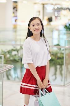 Całkiem uśmiechnięta preteen dziewczyna stojąca w centrum handlowym z torbami na zakupy w rękach