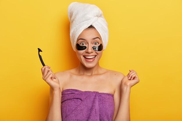 Całkiem wesoła kobieta ma czystą skórę, stoi owinięta ręcznikiem, trzyma żyletkę, przygotowuje się do golenia, wykonuje zabiegi higieniczne, wygląda na wypoczętą, delikatnie się uśmiecha