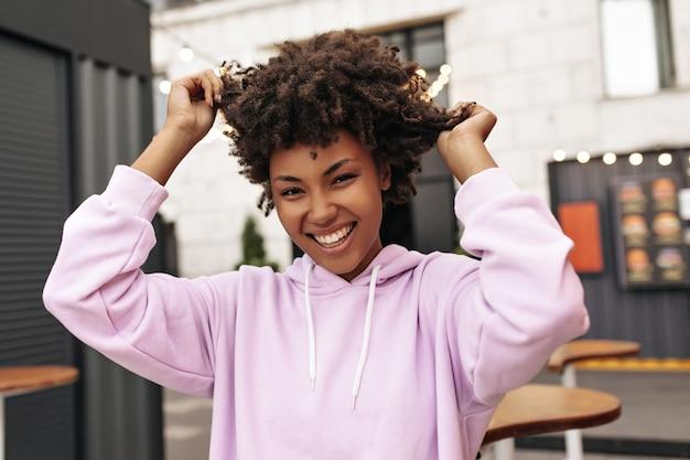 Całkiem wesoła, kręcona brunetka kobieta w modnej różowej bluzie z kapturem, uśmiecha się, patrzy w kamerę i dotyka włosów na zewnątrz