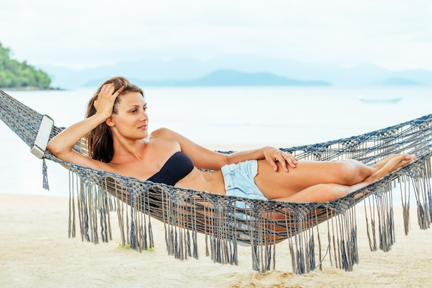 Całkiem wesoła, młoda dziewczyna, leżąc w hamaku na plaży