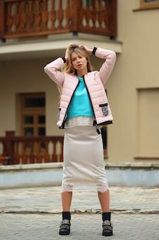 Całkiem zabawna dziewczyna w puchowej kurtce, jedwabnej spódnicy i szorstkich butach pozowanie na zewnątrz