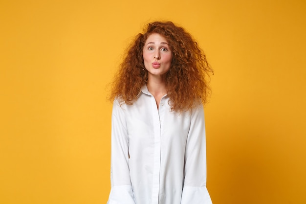Całkiem zabawna młoda rudowłosa kobieta dziewczyna w dorywczo białej koszuli pozuje na żółto pomarańczowej ścianie