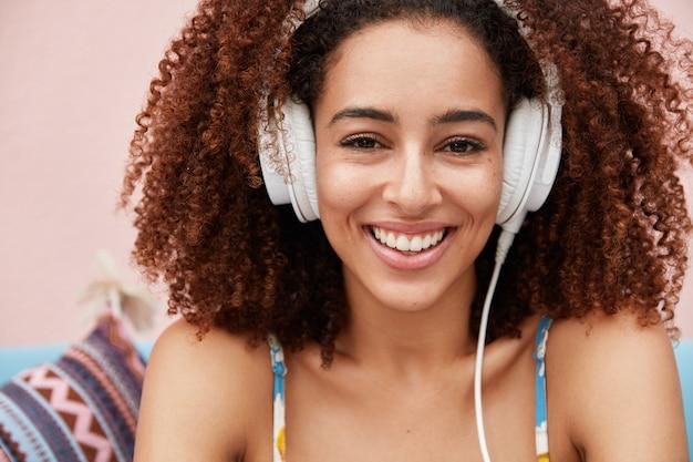 Całkiem zadowolona afroamerykanka o kręconych, krzaczastych włosach lubi ulubioną kompozycję w dużych, nowoczesnych słuchawkach