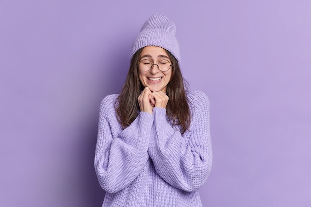 Całkiem zadowolona brunetka trzyma ręce pod brodą i zamyka oczy i jest zachwycona, słysząc coś dobrego w ciepłej zimowej czapce z dużymi okularami.