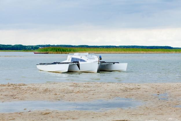 Całkowicie nowy katamaran żaglowy podczas codziennej wycieczki po płytkiej wodzie