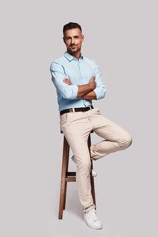 Całkowicie przystojny. pełna długość dobrze wyglądającego młodego mężczyzny uśmiechającego się i trzymającego skrzyżowane ręce siedząc na stołku na szarym tle