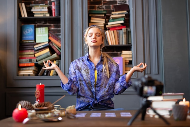 Całkowicie spokojnie. miła spokojna kobieta siedząca z zamkniętymi oczami podczas medytacji