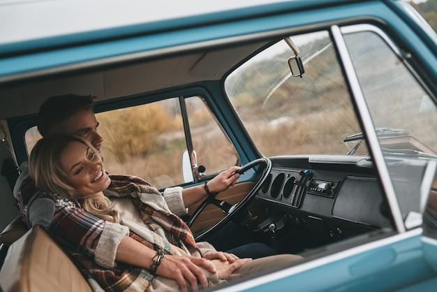Całkowicie szczęśliwy. piękna młoda para obejmując i uśmiechając się siedząc w niebieskim mini vanie w stylu retro