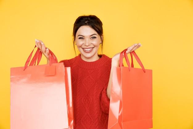 Całkowita sprzedaż. kobieta trzyma czerwone torby na zakupy.