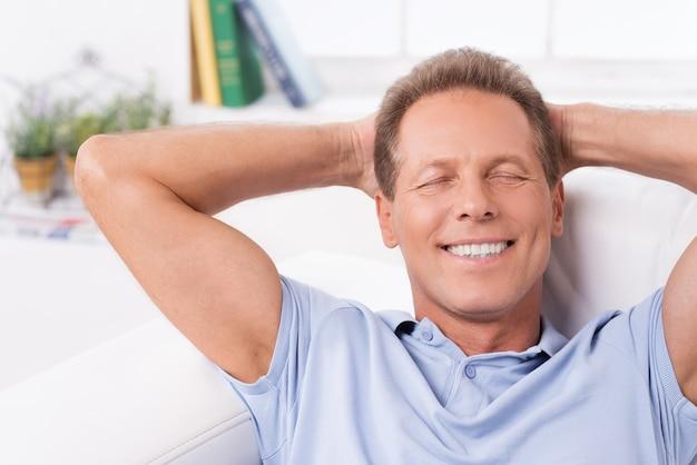 Całkowity relaks. szczęśliwy dojrzały mężczyzna leżący na kanapie i trzymający ręce za głową