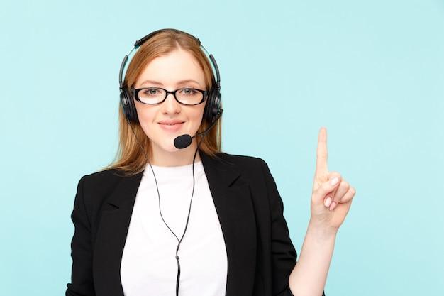 Call center kobieta agenta na białym tle w niebieskim studio wskazując coś w górę.