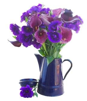 Calla lilly i eustoma kwiaty w niebieskim garnku na białym tle