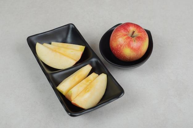 Całość i plasterki czerwonego jabłka na czarnych talerzach