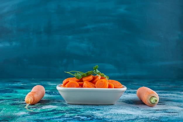 Całość i plasterki marchewki z pietruszką w misce na niebieskim stole.