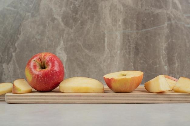 Całość i plastry czerwonego jabłka na desce