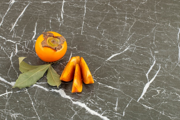 Całość i pokrojona persimmon z liśćmi na czarno