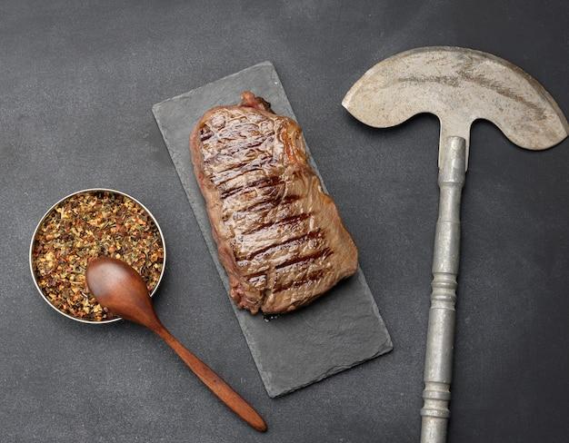 Całość klasyczna pieczeń wołowa na czarnej desce, widok z góry. gotowość mięsa średnio dobra