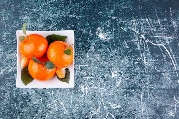 Całość pomarańczowych owoców z zielonymi liśćmi umieszczonymi na białym talerzu.