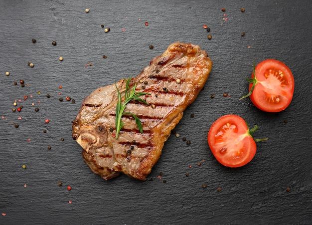 Całość smażona wołowina nowojorska na czarnej desce, rzadki wysmażony rostbef, widok z góry