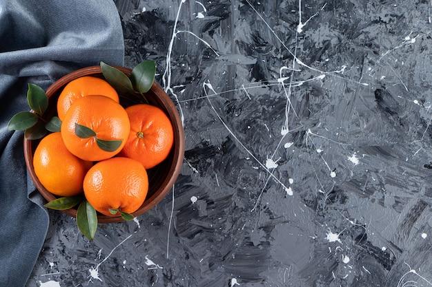 Całość świeżych owoców pomarańczy z liśćmi umieszczonymi na desce.