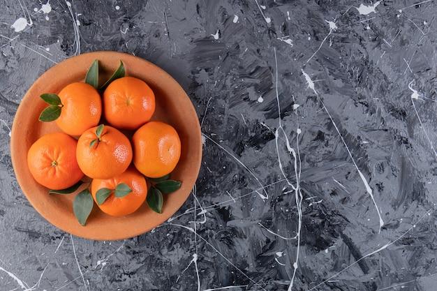 Całość świeżych owoców pomarańczy z liśćmi umieszczonymi w glinianym talerzu.