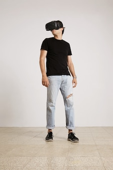 Całościowy portret młodego mężczyzny w goglach vr, czarnej koszulce bez etykiety i niebieskich podartych dżinsach rozglądający się po pokoju z białymi ścianami i jasną drewnianą podłogą
