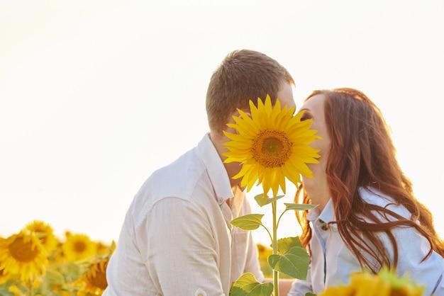 Całowanie młodej pary za słonecznikiem na polu
