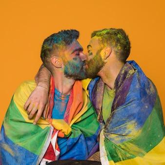Całowanie pary malowanych homoseksualnych mężczyzn owiniętych flagami lgbt