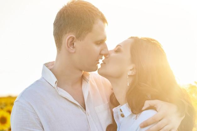 Całowanie portret młodej pary w słonecznikowym polu