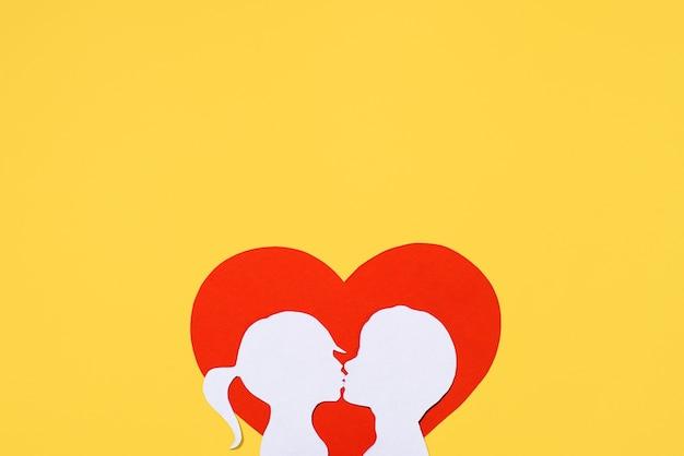 Całowanie sylwetki dziewczyny i chłopca na tle w kształcie serca. koncepcja walentynki. karta kreatywnej miłości. leżał na płasko, widok z góry, miejsce na kopię