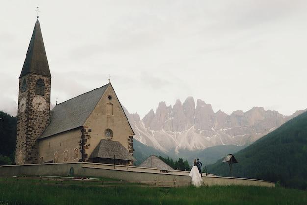 Całuje ślub pary stojaki przed kamiennym kościół w górach