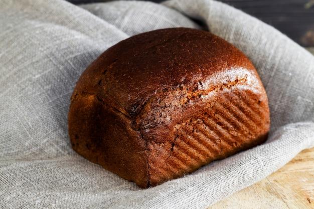 Cały bochenek czarnego chleba na desce do krojenia, zbliżenie domowych wypieków na obrusie