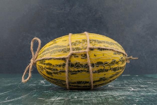Cały dojrzały melon na marmurowej powierzchni.