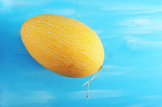 Cały dojrzały żółty melon na drewnianej błękit powierzchni