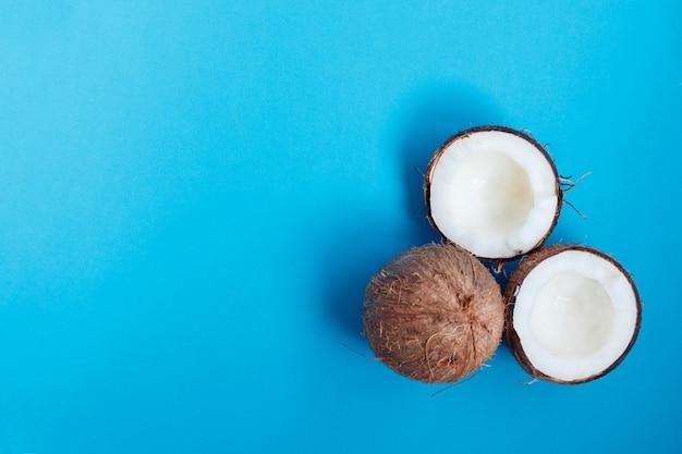 Cały i połówki kokosa na niebieskim tle