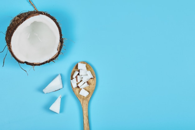 Cały kokos i kawałki kokosa na drewnianej łyżce.
