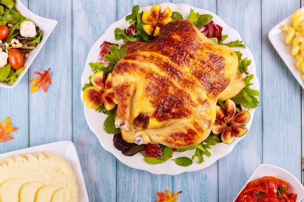 Cały kurczak pieczony na białym talerzu z surówką i fig.