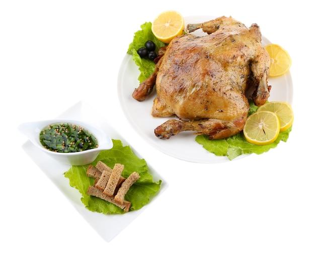 Cały kurczak pieczony z warzywami na talerzu, na białym tle