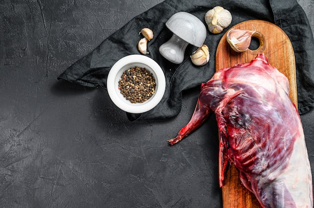 Cały las dziki królik, surowe mięso na drewnianym pokładzie, stary czarny stół rustykalny.
