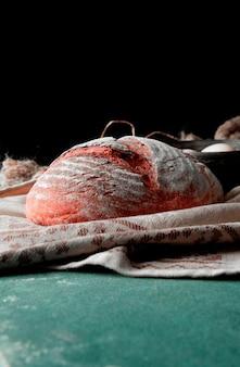 Cały okrągły tradycyjny chleb z mąką na wierzchu na brązowym rustykalnym ręczniku na kamiennym stole.