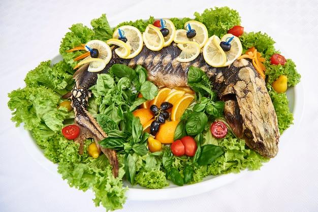 Cały pieczony jesiotr ze świeżymi liśćmi sałaty, warzywami i owocami.