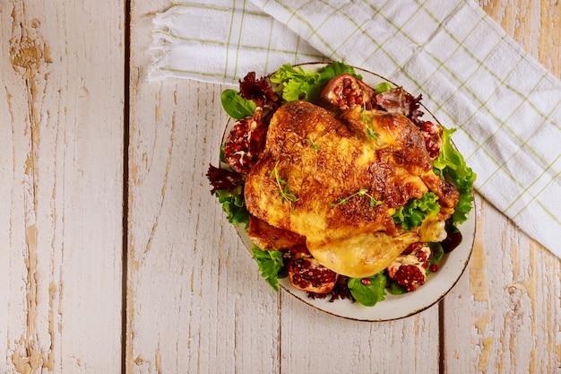 Cały pieczony kurczak na talerzu z sałatką i granatem