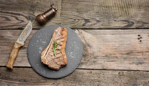 Cały smażony stek wołowy nowojorski na czarnej desce, wysmażony rostbef krwisty, widok z góry, miejsce na kopię