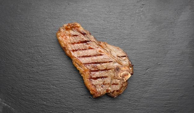 Cały smażony stek z nowojorskiej wołowiny na czarnej desce, wysmażony rostbef krwisty, widok z góry