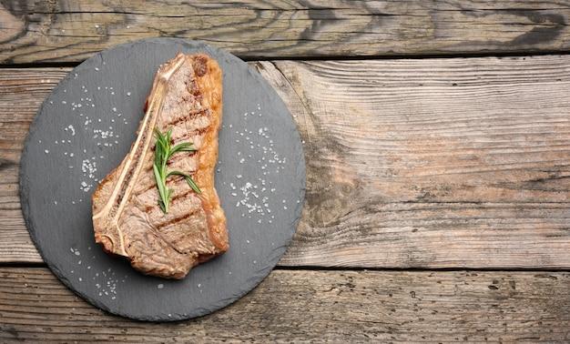 Cały stek wołowy nowojorski smażony na czarnej desce, rostbef wysmażony rzadki, widok z góry, miejsce na kopię