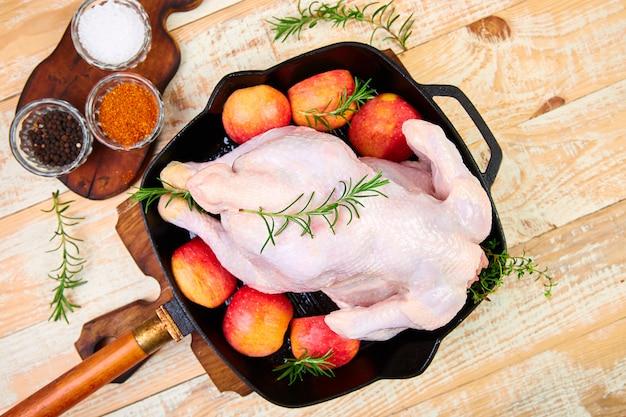 Cały surowy kurczak z dodatkami. gotowanie w tle.
