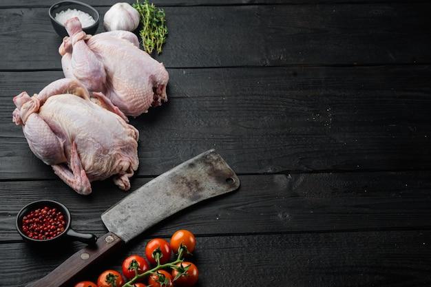 Cały surowy kurczak z wolnego wybiegu z dodatkami ziół i przypraw, na czarnym drewnie