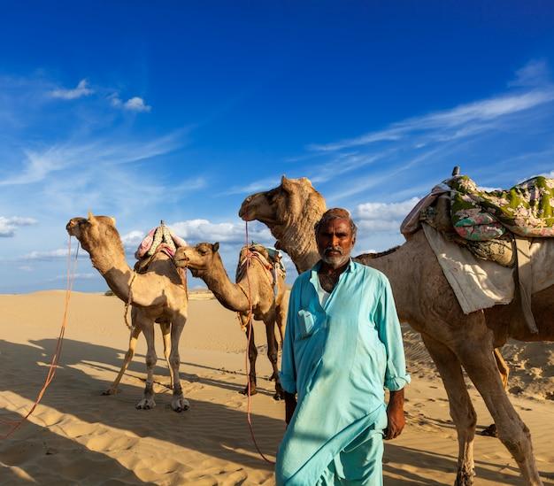 Cameleer (kierowca wielbłądów) z wielbłądami na wydmach pustyni thar. raj