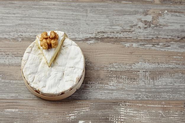 Camembert w drewnianym pudełku na tle nieczysty stół
