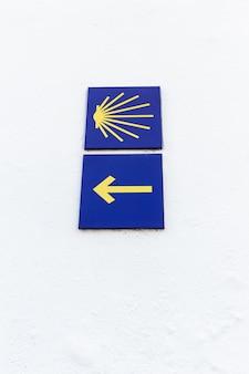 Camino de santiago żółty przegrzebek i znak strzałki na białej ścianie.